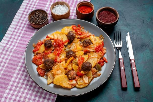 Draufsicht gekochte geschnittene kartoffeln mit fleischbällchen zusammen mit gewürzen auf dem dunkelblauen hintergrund.