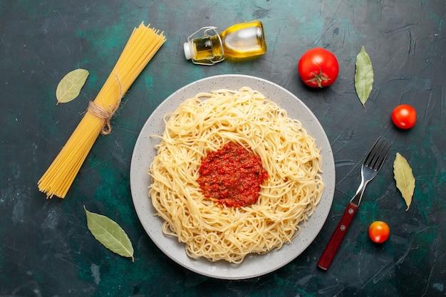 Draufsicht gekochte italienische nudeln mit gehacktem tomatenfleisch auf dem dunkelblauen schreibtisch