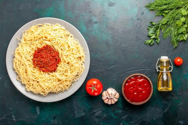 Draufsicht gekochte italienische nudeln mit gehacktem tomatenfleisch und öl auf dunklem schreibtisch