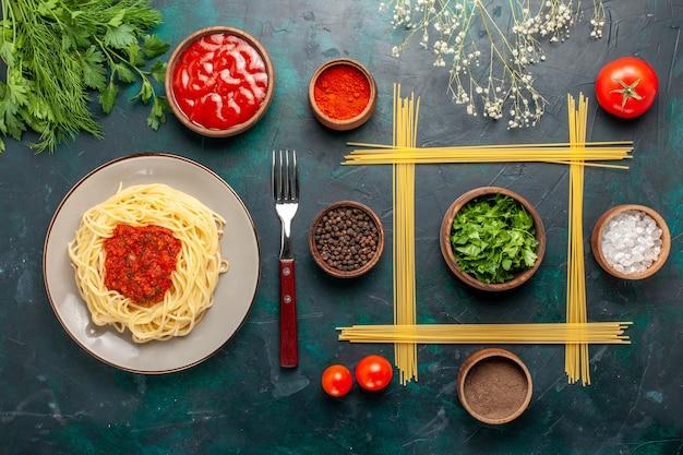 Draufsicht gekochte italienische nudeln mit hackfleisch der tomatensauce und verschiedenen gewürzen auf dunkelblauer oberfläche