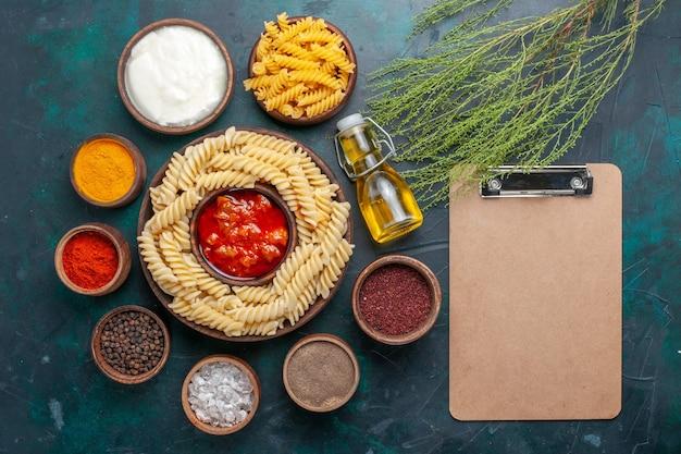 Draufsicht gekochte italienische nudeln mit saucenblock und gewürzen auf dunkler oberfläche