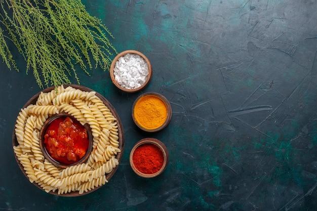 Draufsicht gekochte italienische nudeln mit soße und verschiedenen gewürzen auf dunklem schreibtisch