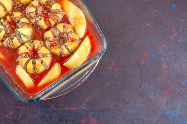 Draufsicht gekochte kartoffeln mit soße und hackfleisch auf dunklem hintergrund.