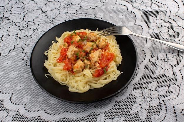 Draufsicht gekochte nudeln lecker mit hühnchenscheiben und tomatensauce in schwarzer platte auf dem tisch