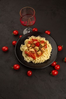 Draufsicht gekochte nudeln mit hühnerflügeln und tomatensauce in schwarzer platte auf dem dunklen boden
