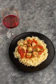 Draufsicht gekochte nudeln mit hühnerflügeln und tomatensauce in schwarzer platte auf dem grauen