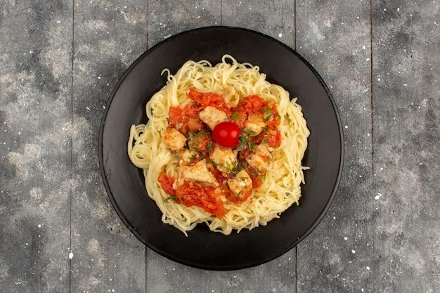 Draufsicht gekochte nudeln mit tomatensaucen und geschnittenen hühnerflügeln in schwarzer platte auf dem grauen rustikalen holzboden