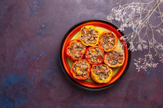 Draufsicht gekochte paprika mit hackfleisch innerhalb platte auf dunkelgrauem oberflächenfutter dolma gemüsemehl rindfleisch