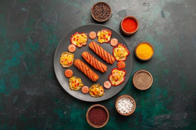 Draufsicht gekochte paprika mit würstchen und gewürzen auf der dunkelgrünen oberfläche