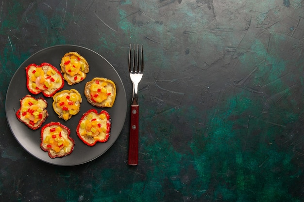 Draufsicht gekochte paprika zum mittagessen in grauer platte auf dunkelgrüner oberfläche