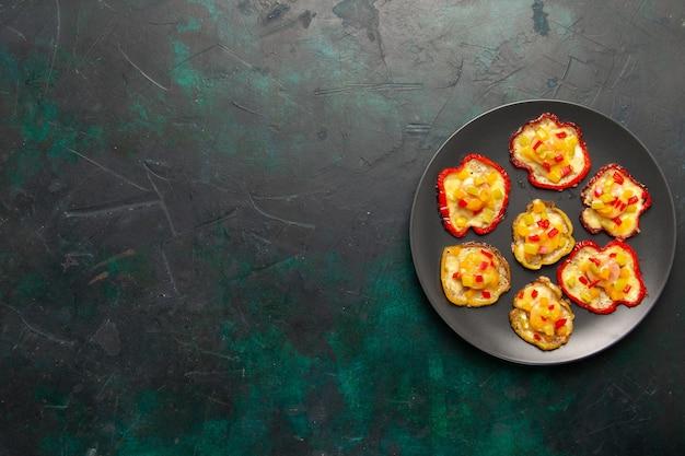 Draufsicht gekochte paprika zum mittagessen innerhalb teller auf der dunklen oberfläche