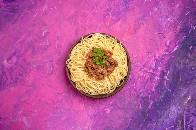 Draufsicht gekochte spaghetti mit hackfleisch auf dem rosafarbenen tafelteigmahlzeit-nudelgericht