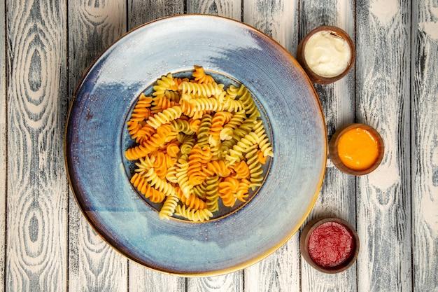 Draufsicht gekochte spiralnudeln mit verschiedenen gewürzen auf dem grauen schreibtisch nudelteig farbe pfeffer essen