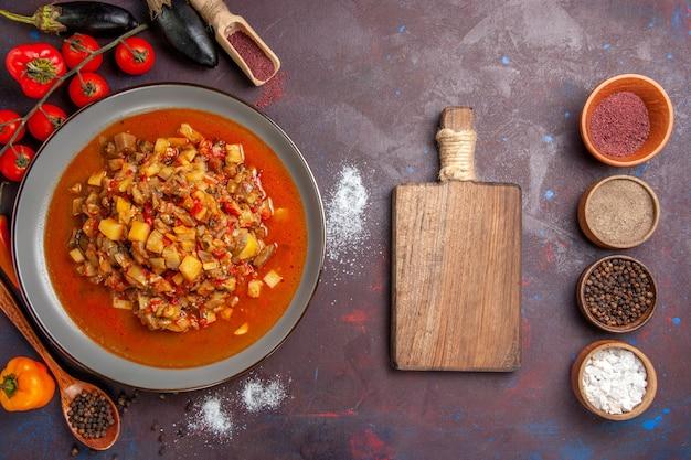 Draufsicht gekochtes gemüse geschnitten mit soße und gewürzen auf dem dunklen hintergrund mahlzeit essen abendessen suppe sauce gemüse