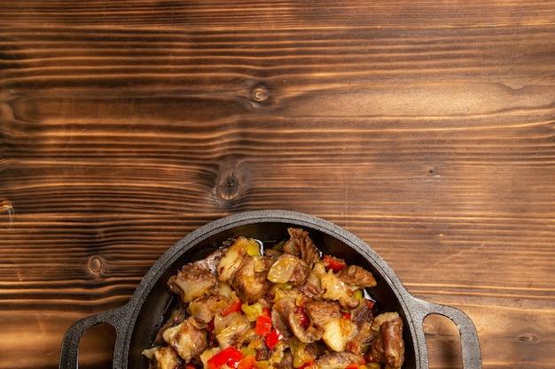 Draufsicht gekochtes gemüsemehl mit fleisch und geschnittenem paprika auf holzschreibtisch