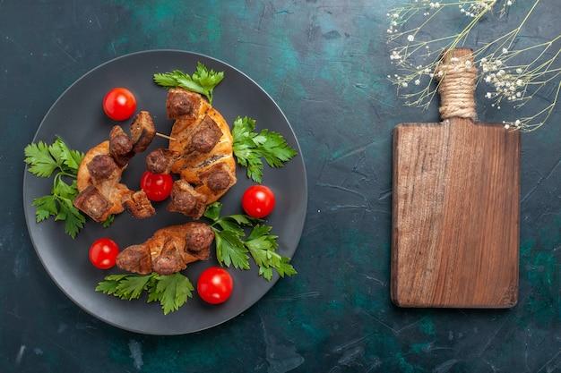 Draufsicht gekochtes geschnittenes fleisch mit gemüse und roten kirschtomaten auf der dunkelblauen oberfläche