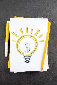 Draufsicht gelb ideallight glühbirne geschrieben auf notizblock gelber marker und bleistift auf schwarz