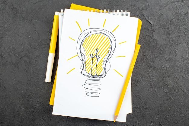 Draufsicht gelb ideallight glühbirne zeichnung auf notizblock marker und bleistift auf schwarz