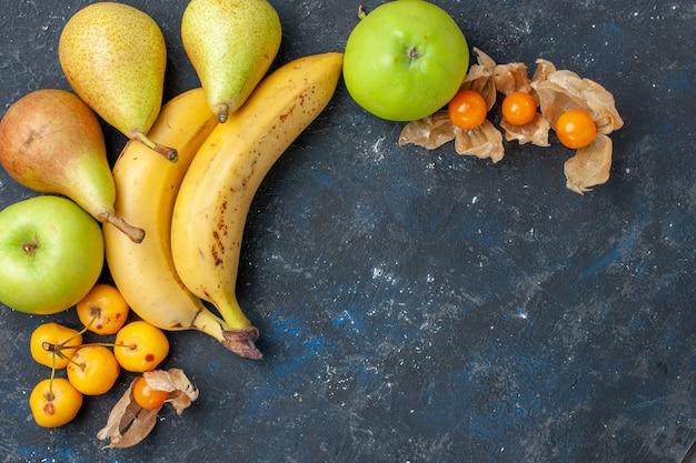 Draufsicht gelbe bananen paar beeren mit frischen grünen apfelbirnen auf dem dunkelblauen schreibtisch obstbeere frisches vitamin süß