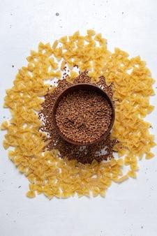 Draufsicht gelbe rohe nudeln wenig mit teller buchweizen auf dem weißen schreibtisch nudeln italien essen mahlzeit