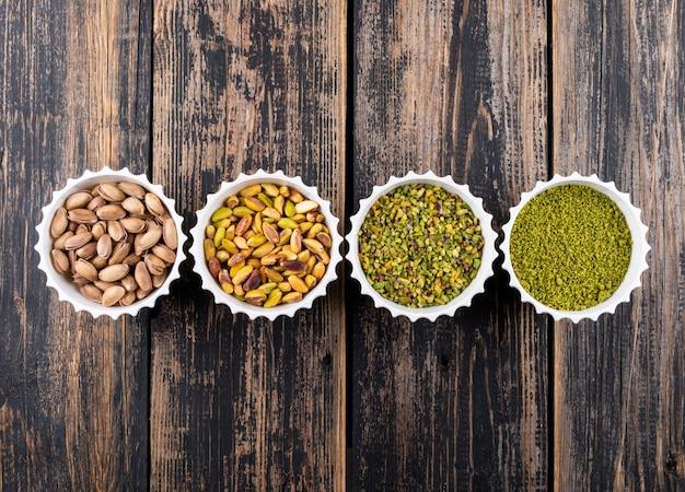 Draufsicht gemahlene, gemahlene, zerkleinerte oder granulierte pistazien in schalen auf dunklem holz