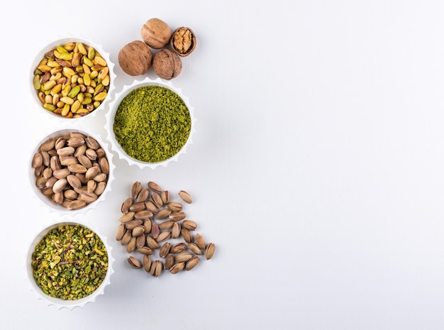 Draufsicht gemahlene, gemahlene, zerkleinerte oder granulierte pistazien in schalen auf weiß