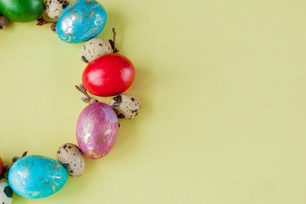 Draufsicht gemalte eier-osterrahmen in kreisform auf gelbem hintergrund. speicherplatz kopieren.