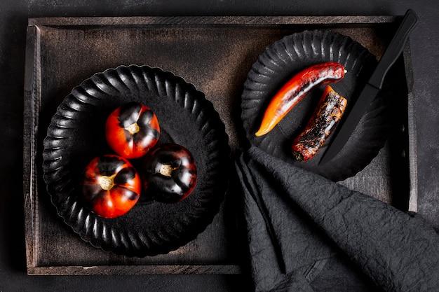 Draufsicht gemalte schwarze gebackene tomaten und paprikapfeffer