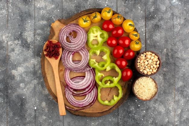 Draufsicht gemüse bunt geschnitten und ganze zwiebeln grüne paprika tomaten auf dem braunen schreibtisch und grau rustikalem boden