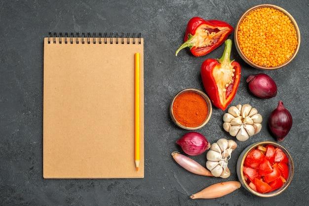 Draufsicht gemüse notebook bleistift paprika zwiebel tomaten gewürze knoblauch