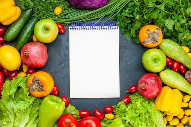 Draufsicht gemüse und obst salat tomaten gurke dill kirsche tomaten zucchini granatapfel persimone apfel notizbuch in der mitte