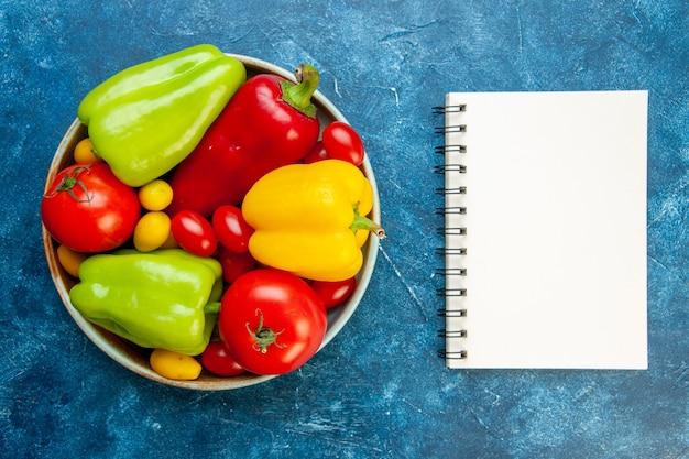 Draufsicht gemüse verschiedene farben paprika tomaten kirschtomaten in schüssel notizblock auf blauem tisch