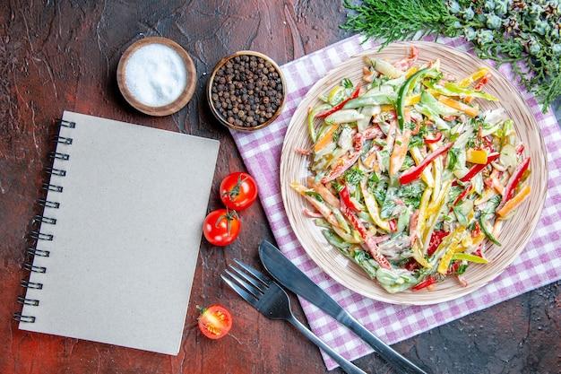 Draufsicht gemüsesalat auf teller auf tischdecke gabel und messersalz und tomaten mit schwarzem pfeffer ein notizbuch auf dunkelrotem tisch