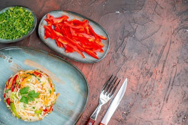 Draufsicht-gemüsesalat mit grüns und geschnittener paprika auf dunklem tisch