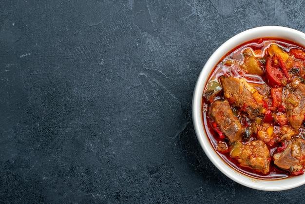 Draufsicht gemüsesuppe mit fleisch innerhalb platte auf dunkelgrau