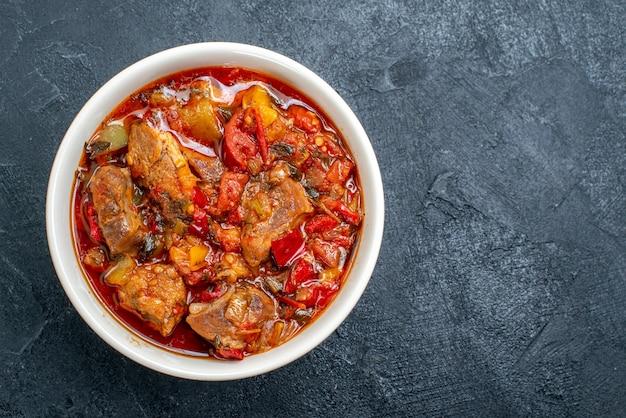 Draufsicht gemüsesuppe mit fleisch innerhalb platte auf grau
