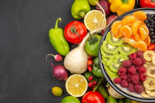 Draufsicht gemüsezusammensetzung frisches gemüse mit geschnittenen früchten auf dunklem hintergrund leben pflanzen reife diät lebensmittel salat farbe