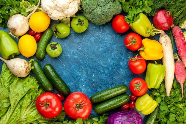 Draufsicht gemüsezusammensetzung mit frischen früchten auf blauem schreibtisch mahlzeit diät salat gesundes leben reife farbe