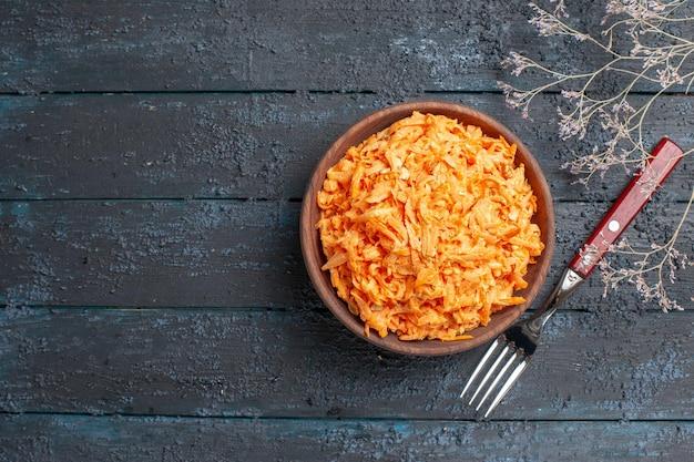 Draufsicht geriebener karottensalat in brauner platte auf dem dunkelblauen rustikalen schreibtisch gesundheit salat reife gemüsediätfarbe
