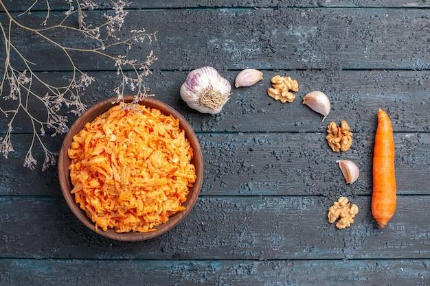 Draufsicht geriebener karottensalat mit knoblauch im teller auf dunkelblauem rustikalem schreibtisch gesundheit farbsalat reife gemüsediät