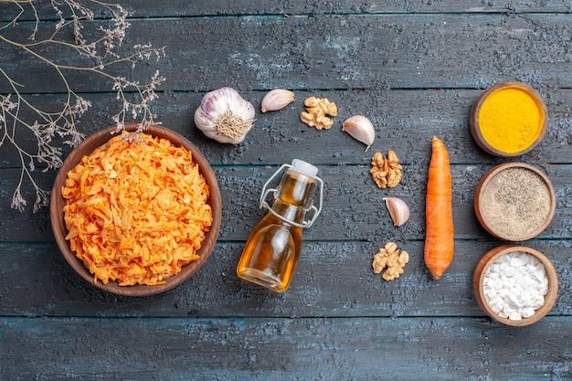 Draufsicht geriebener karottensalat mit knoblauch und gewürzen auf dem dunkelblauen rustikalen schreibtisch gesundheit farbsalat reife gemüsediät