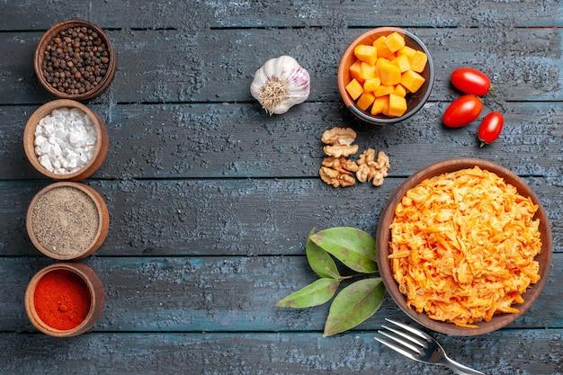 Draufsicht geriebener karottensalat mit knoblauchwalnüssen und gewürzen auf dem dunklen schreibtisch gesundheit diätsalat orange farbe reif