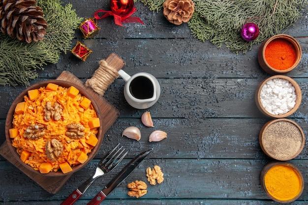 Draufsicht geriebener karottensalat mit walnüssen und gewürzen auf dunkelblauem schreibtisch naturkostsalat diät nüsse farbe