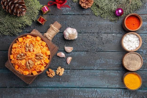 Draufsicht geriebener karottensalat mit walnüssen und gewürzen auf dunkelblauem schreibtisch naturkostsalat farbdiätnuss