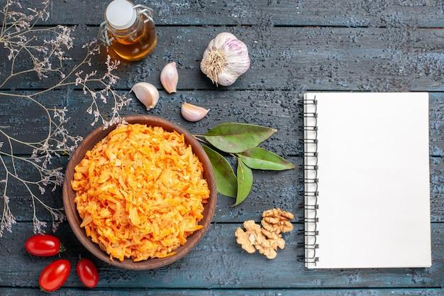 Draufsicht geriebener karottensalat mit walnüssen und knoblauch auf dem dunklen hintergrund gesundheit diät orange farbe reifer salat