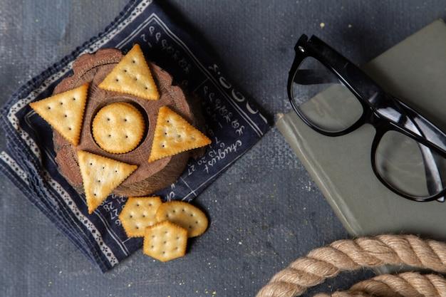 Draufsicht gesalzene cracker mit seilen und sonnenbrille auf dem grauen hintergrund knackigen crackerfoto-snack