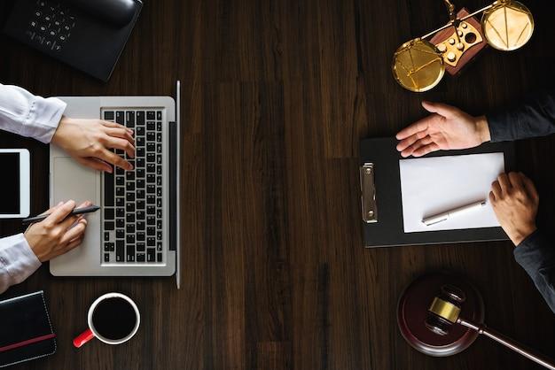 Draufsicht geschäft und anwälte diskutieren vertragspapiere mit messingskala auf dem schreibtisch im büro. recht, rechtsdienstleistungen, beratung, justiz und rechtskonzept.