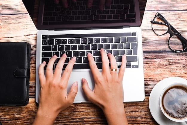 Draufsicht geschäftsfrau, die auf laptop am arbeitsplatz tippt. frau, die im heimbüro hand tastatur arbeitet. arbeitsplatzkonzept
