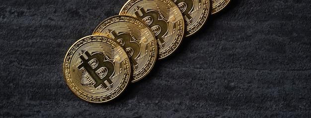 Draufsicht-geschäftskonzept des bitcoin-kryptowährungsgeldes auf dunklem schwarzem schiefertabellenhintergrund.