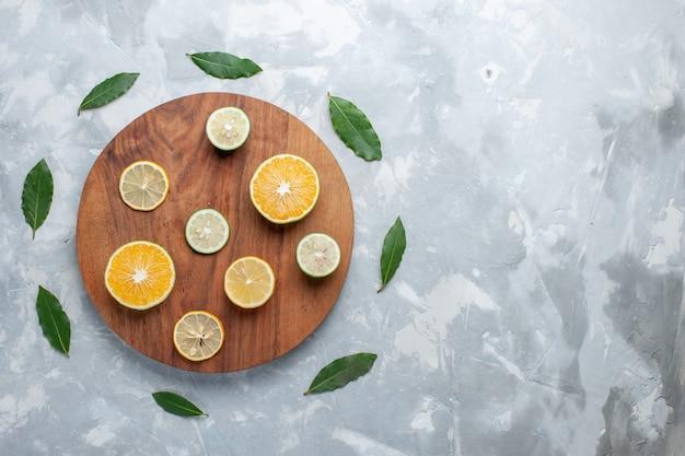 Draufsicht geschnittene frische zitronen saftige zitrusfrüchte auf leichtem schreibtischfrucht frischem zitronensaft sauer